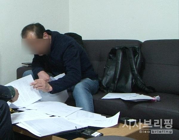 청원인 A씨가 그동안 진행됐던 일련의 상황들에 대해 관련 서류들을 놓고 설명을 하고 있다./출처=전수용 기자